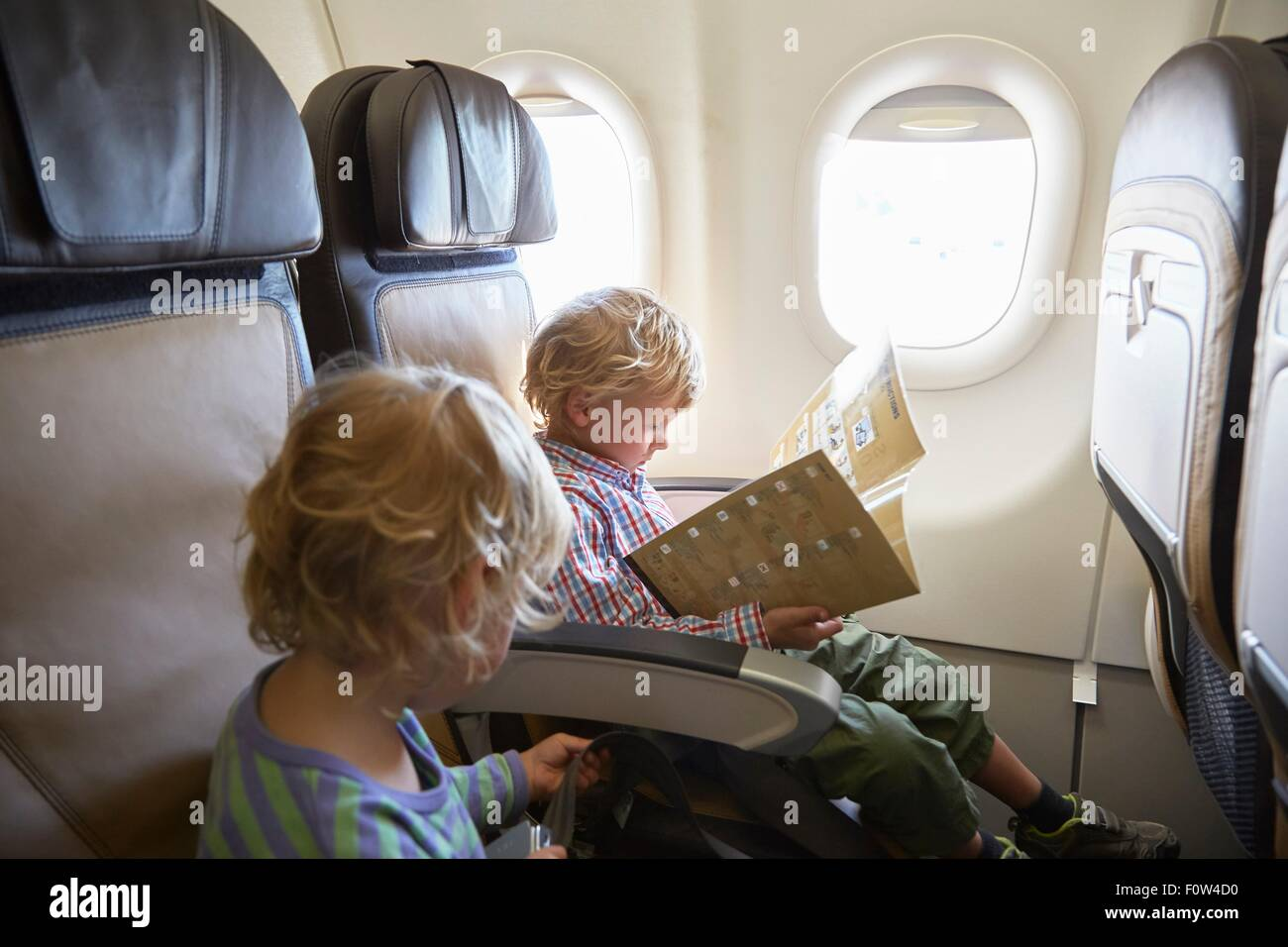 Boys seated in airplane - Stock Image