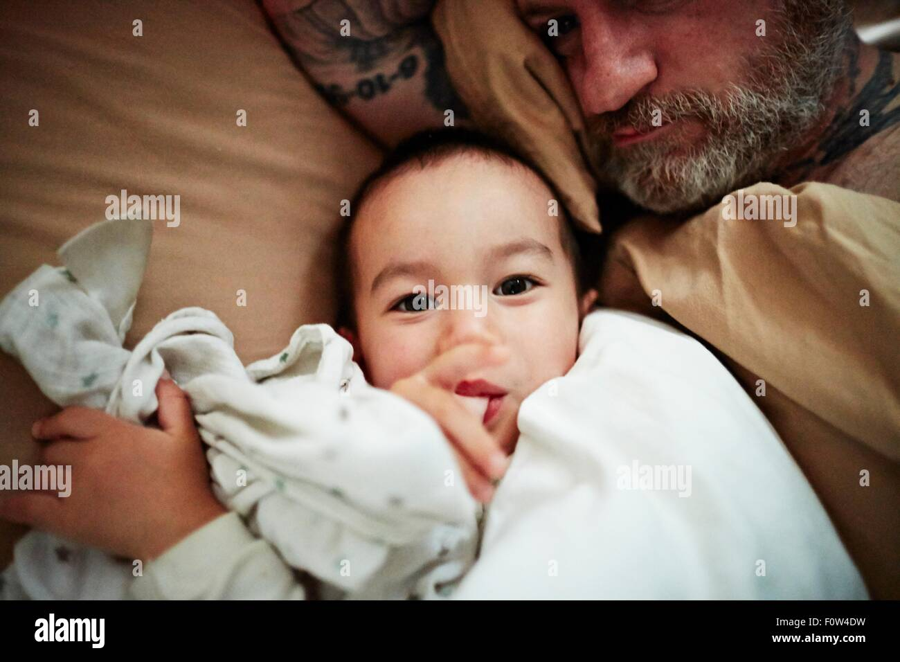 Father and son lying down on bed - Stock Image