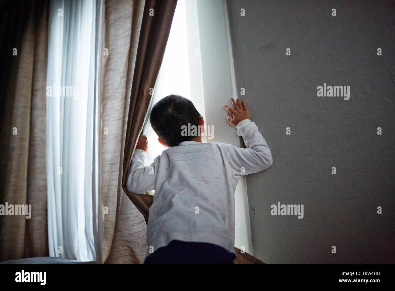Boy peeking out from curtain - Stock Image