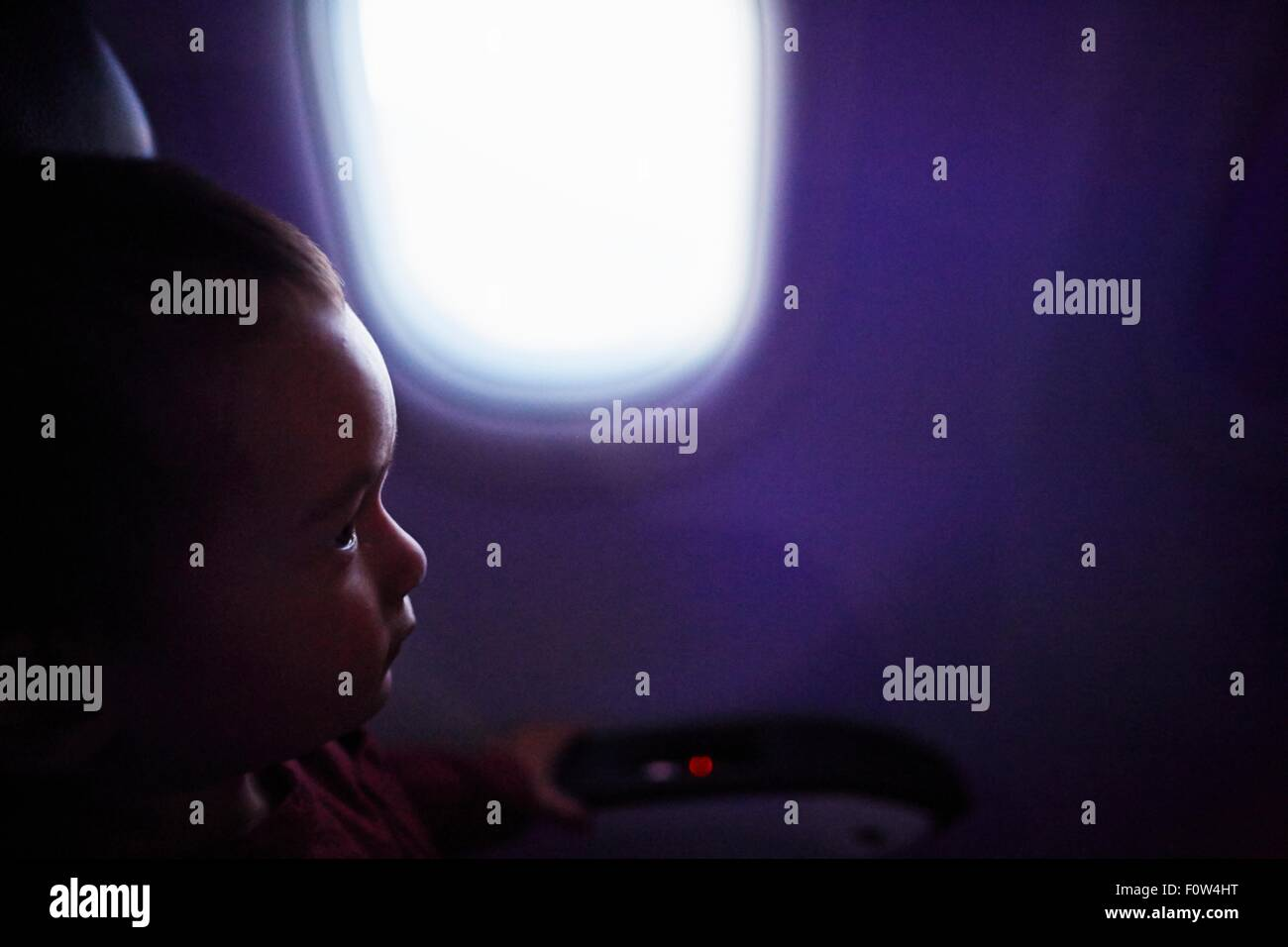 Boy seated inside airplane - Stock Image