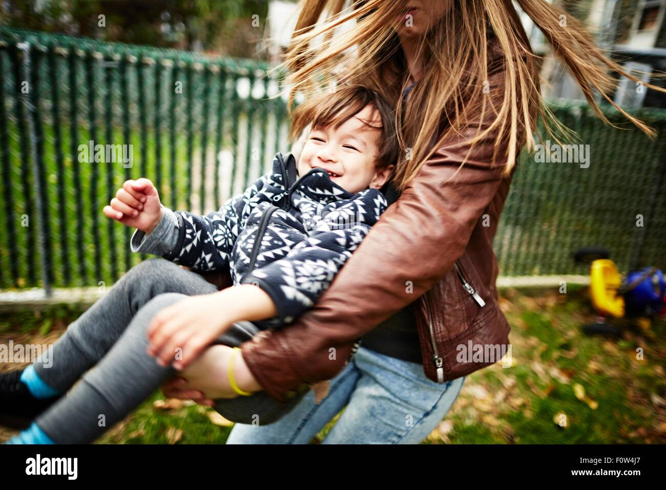 Mother playing with son in garden - Stock Image