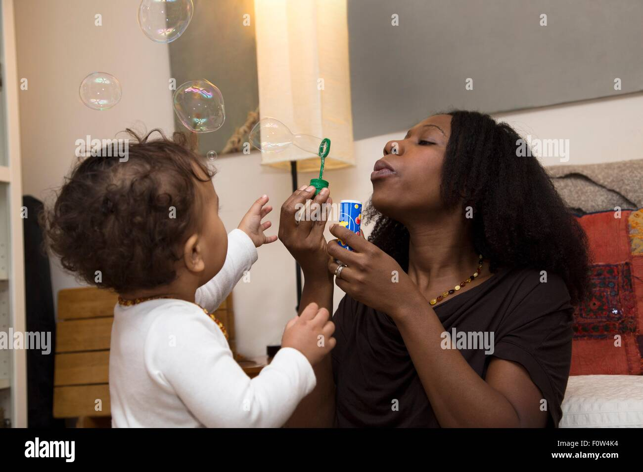 Mid adult woman and toddler daughter blowing bubbles Stock Photo