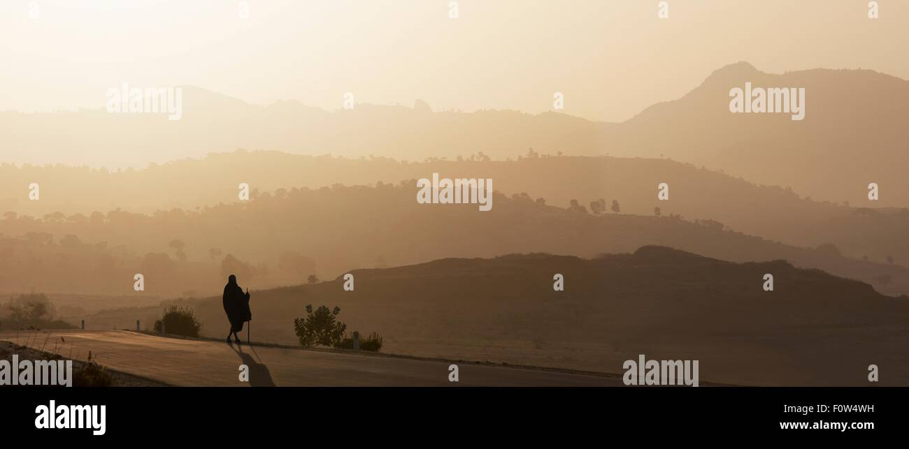 Rear view of senior man in traditional clothing looking out over landscape at sunset, Ethiopia, Africa - Stock Image