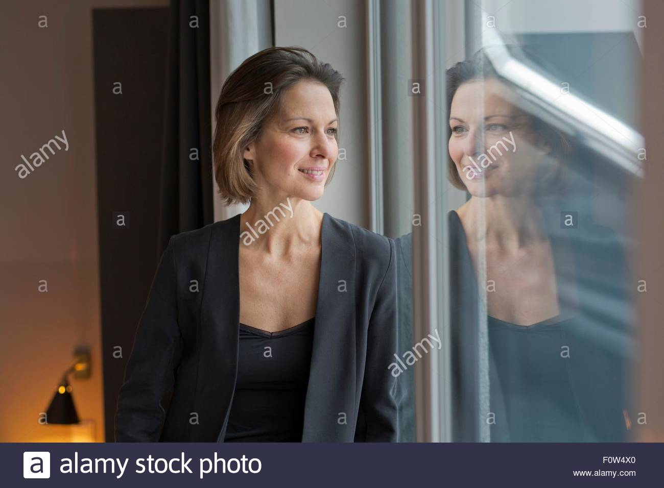 Portrait of mature woman gazing out of apartment window - Stock Image
