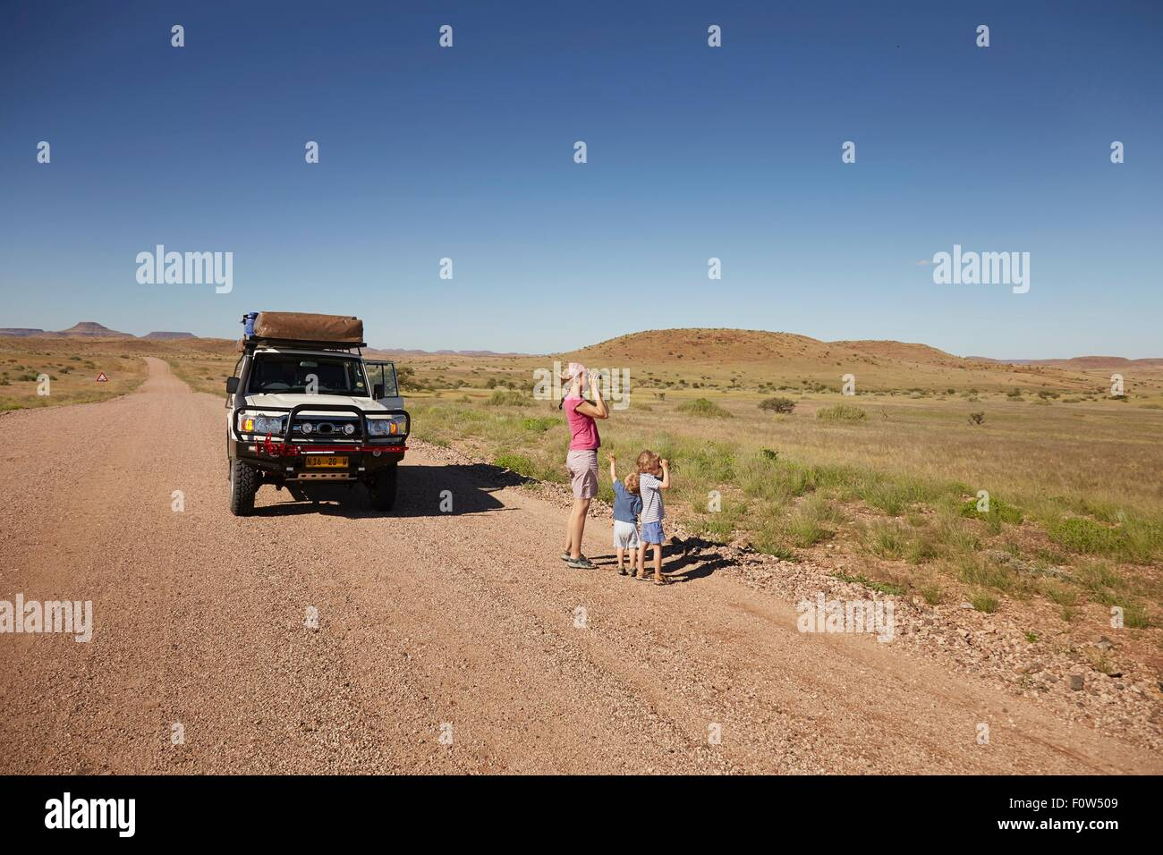 Off road vehicle parked while mother and children look at view, Sesfontein, Kaokoland, Namibia - Stock Image