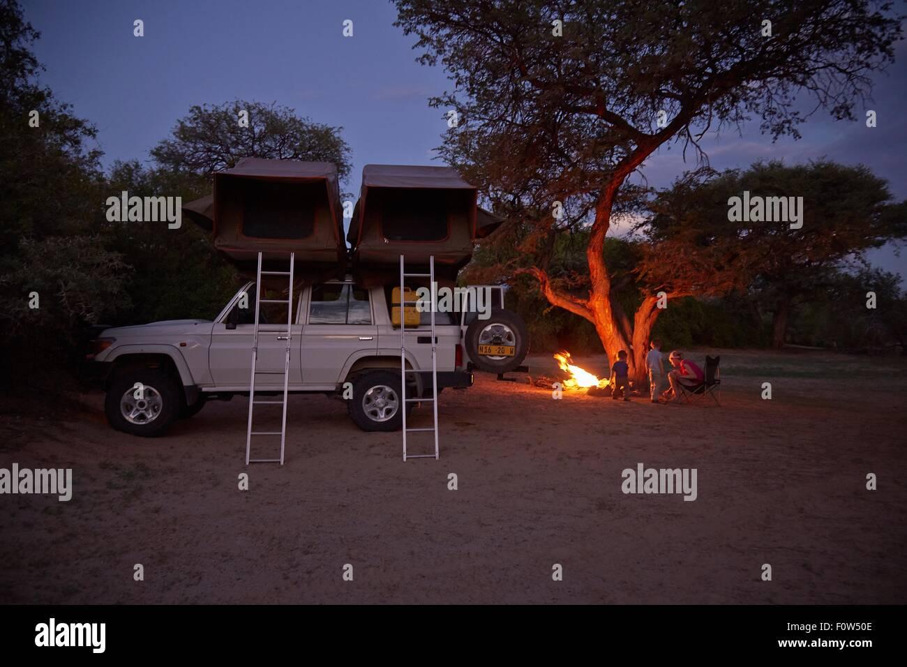 Off road vehicle parked, family sitting around campfire, Purros, Kaokoland, Namibia - Stock Image