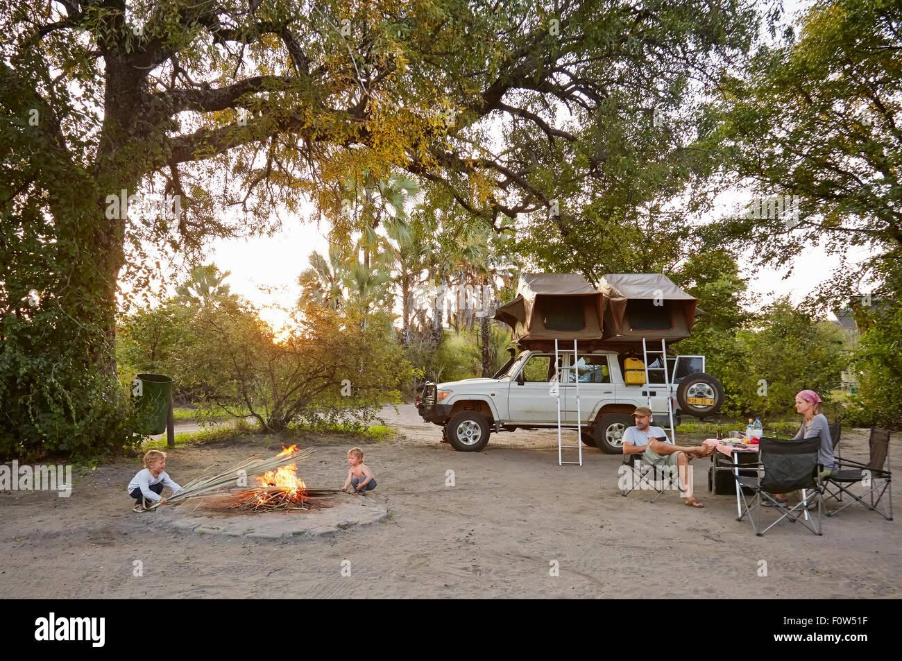 Off road vehicle parked, family relaxing around camp fire, Nata, Makgadikgadi, Botswana - Stock Image