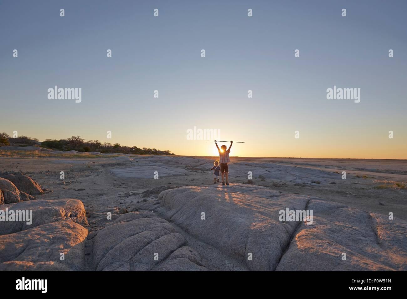 Two boys standing on rock, holding spear in air, sunset, Gweta, makgadikgadi, Botswana - Stock Image