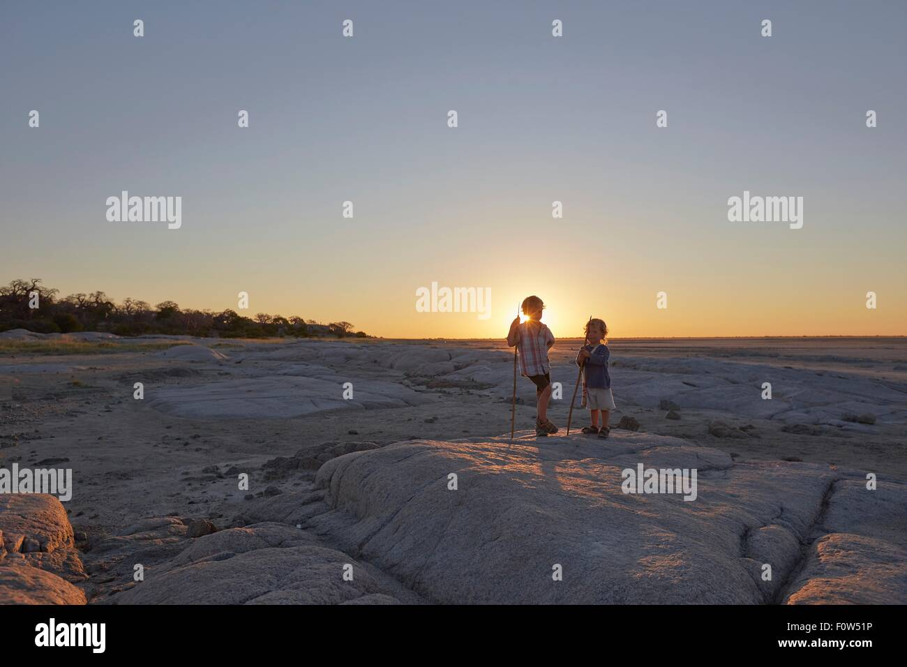 Two boys standing on rock, holding spear, sunset, Gweta, makgadikgadi, Botswana Stock Photo