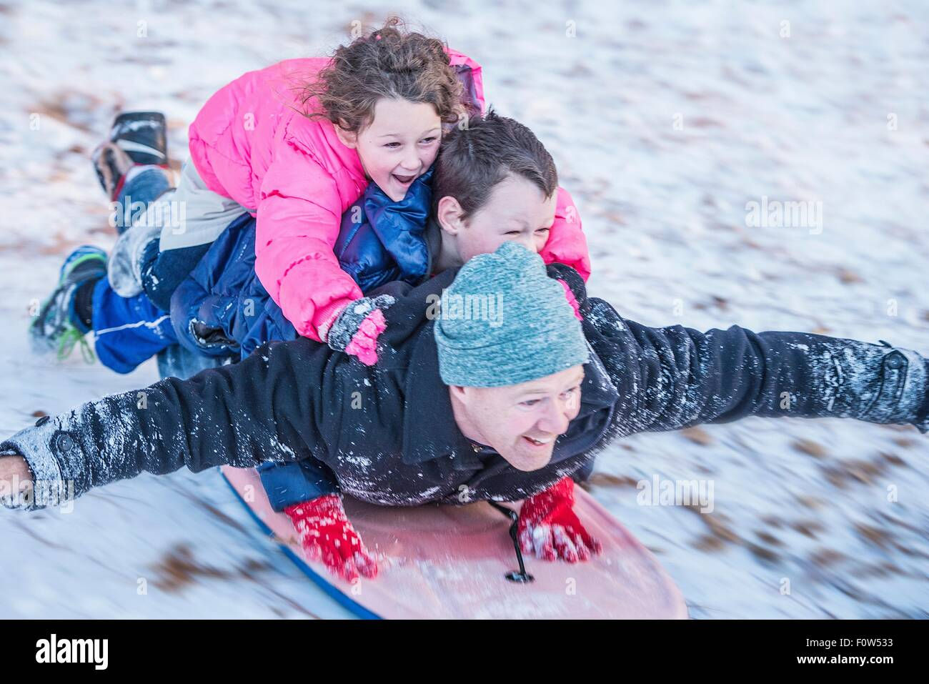 Portrait of father, son and daughter laying on top of each other riding sledge down hill - Stock Image