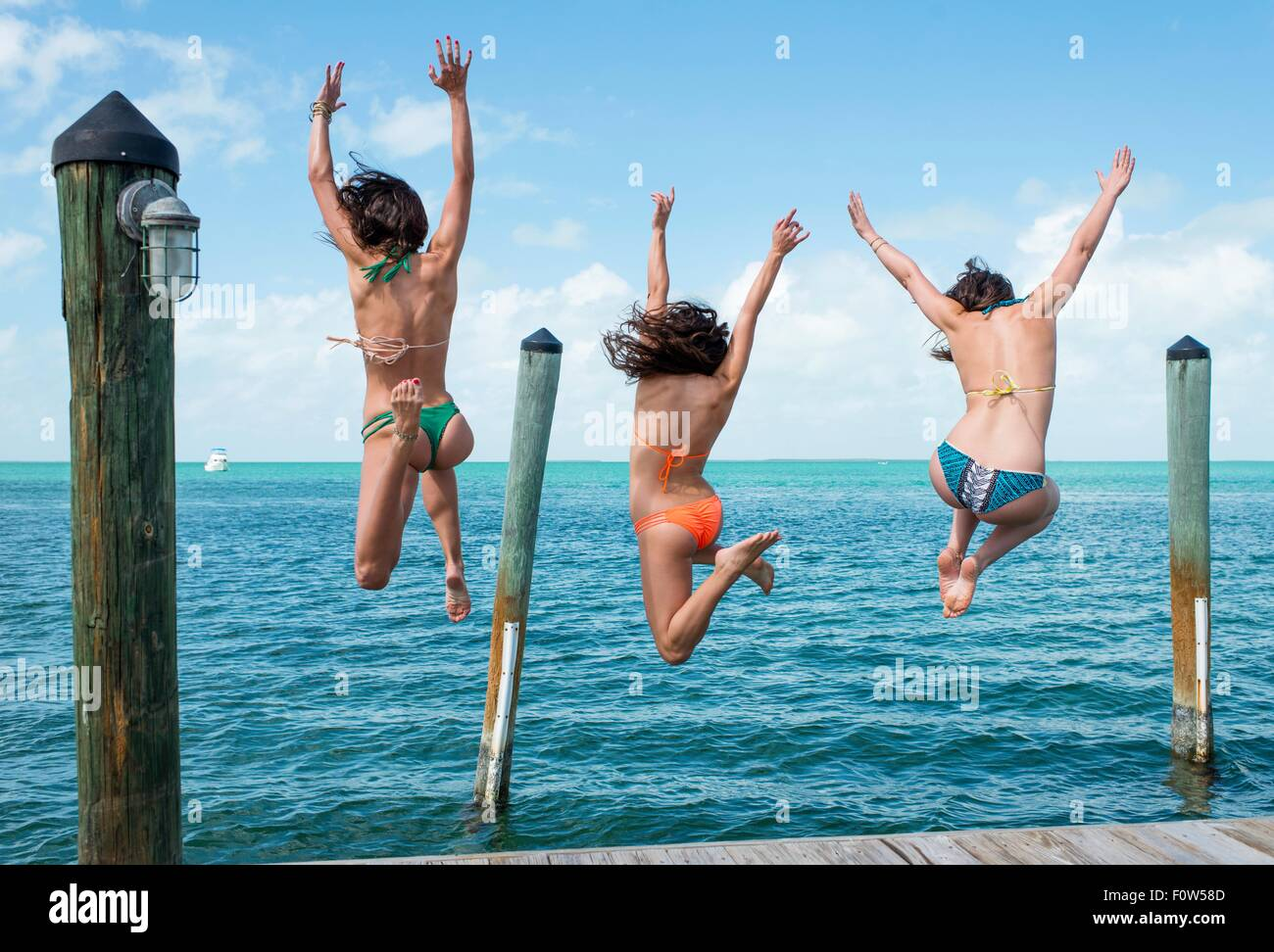Rear view of three young woman jumping from sea pier, Islamorada, Florida, USA - Stock Image