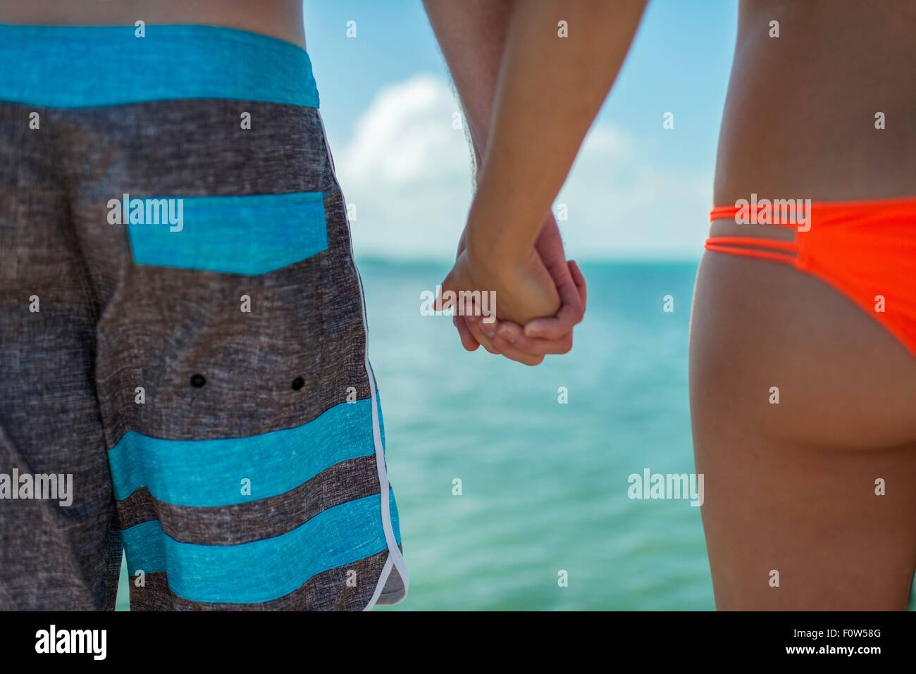 Cropped view of young couple holding hands in front of blue sea, Islamorada, Florida, USA - Stock Image