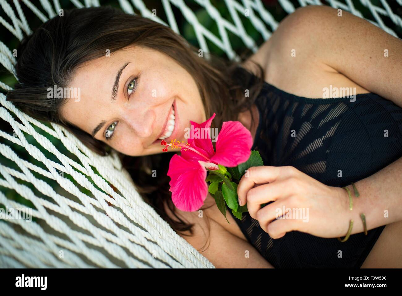 Portrait of young woman on hammock with pink flower - Stock Image