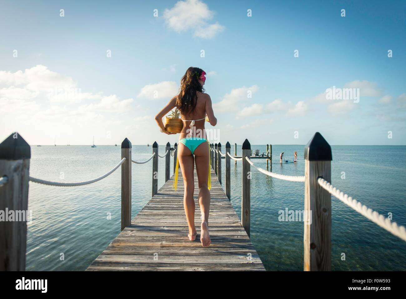 Rear view of young woman on sea pier carrying bowl of fruit, Islamorada, Florida, USA - Stock Image
