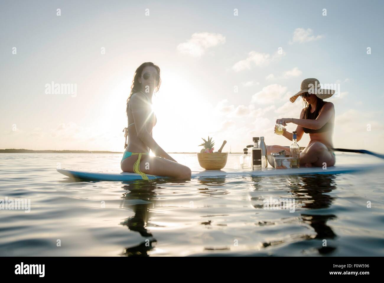 Two young women preparing cocktails on paddleboard, Islamorada, Florida, USA - Stock Image