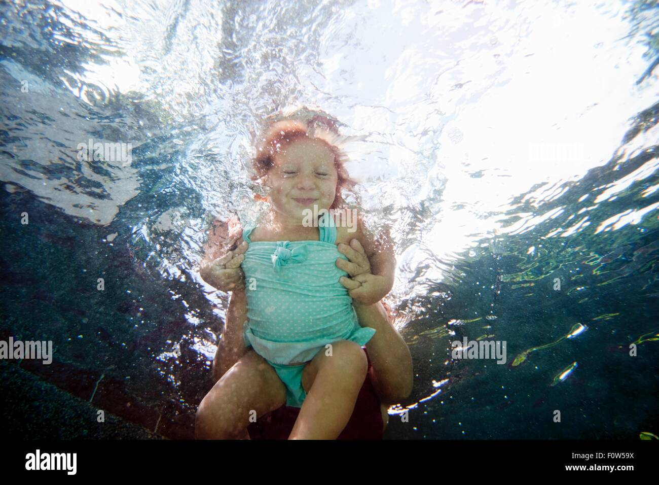 Underwater portrait of girl learning to swim and smiling at camera - Stock Image