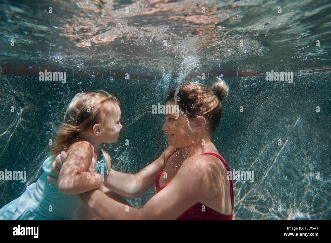 Underwater shot of mother holding daughter and helping her to learn to swim - Stock Image