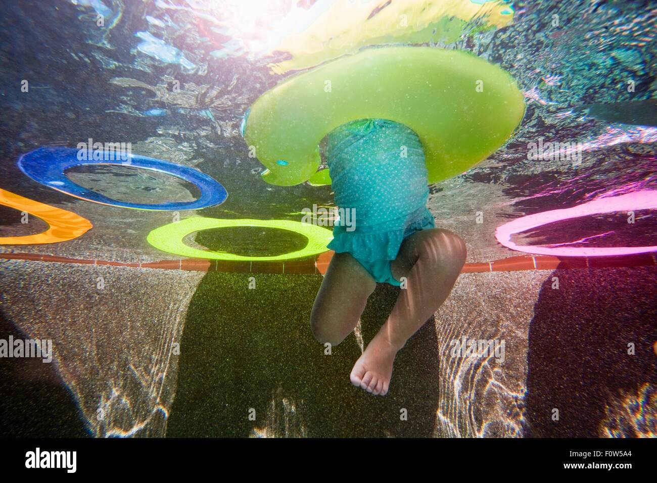 Underwater shot of girl kicking legs in swimming pool learning to swim with rubber ring - Stock Image