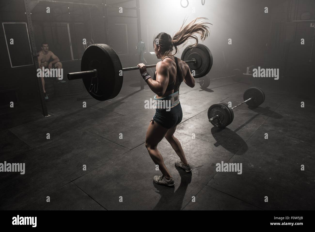 Young woman lifting barbell, rear view Stock Photo
