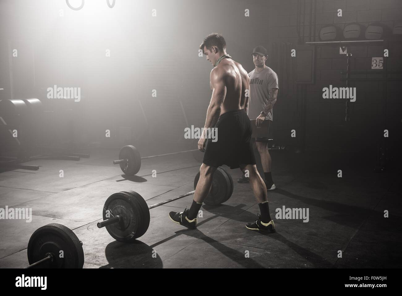 Mid adult man about to lift barbell, while trainer looks on - Stock Image