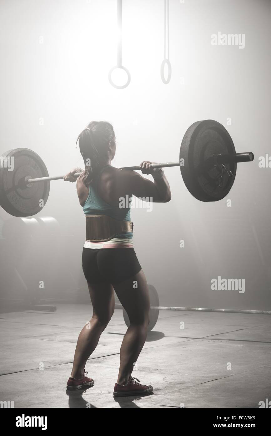 Young woman lifting barbell, rear view - Stock Image