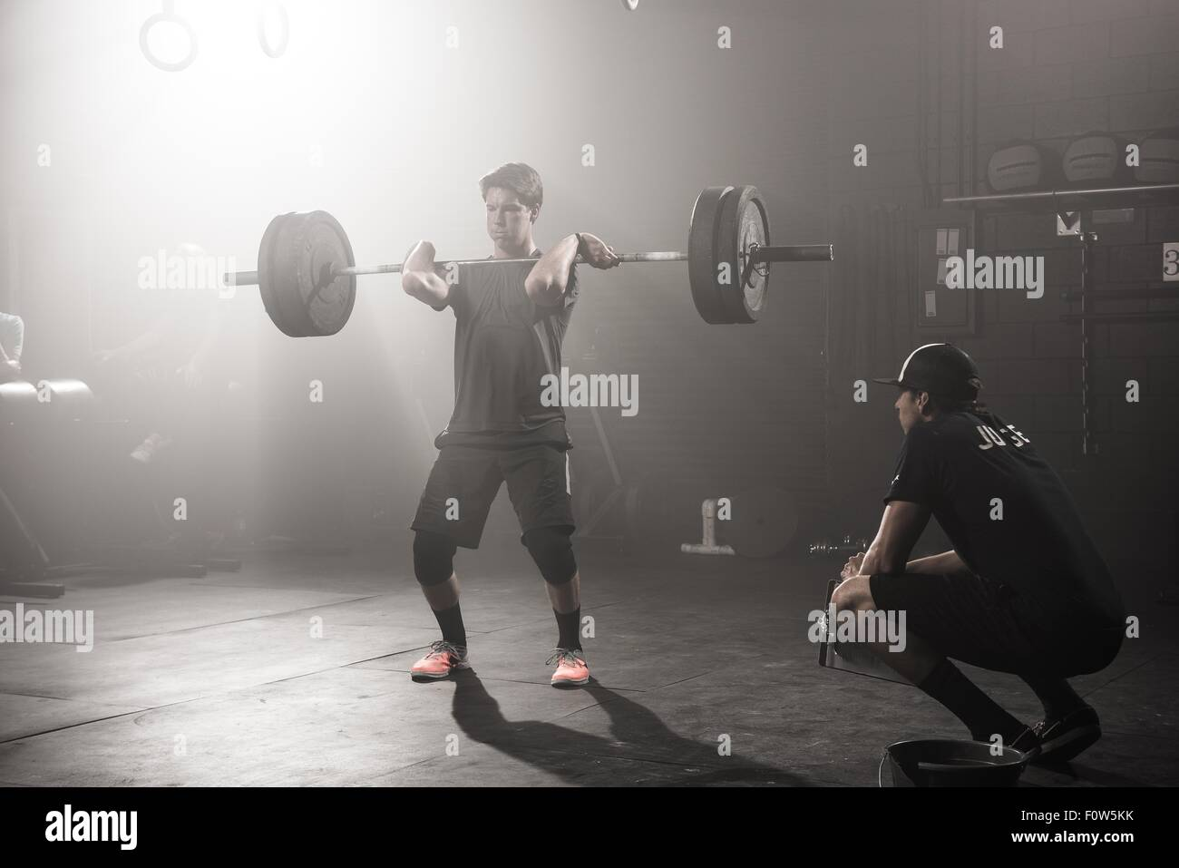 Young man lifting barbell while trainer looks on Stock Photo