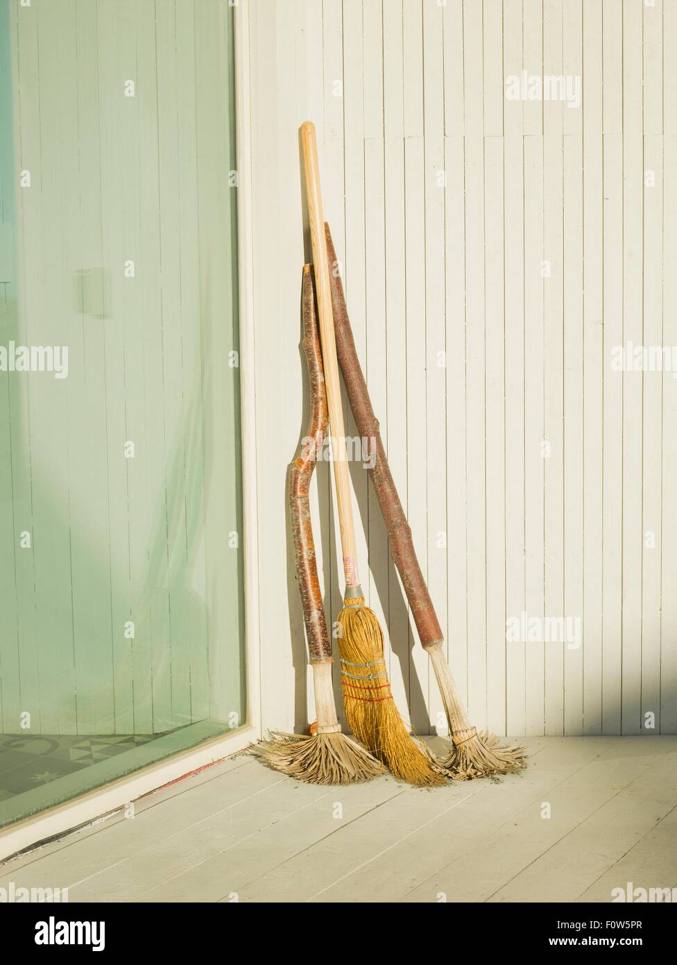 Brooms and mops leaning against patio door - Stock Image