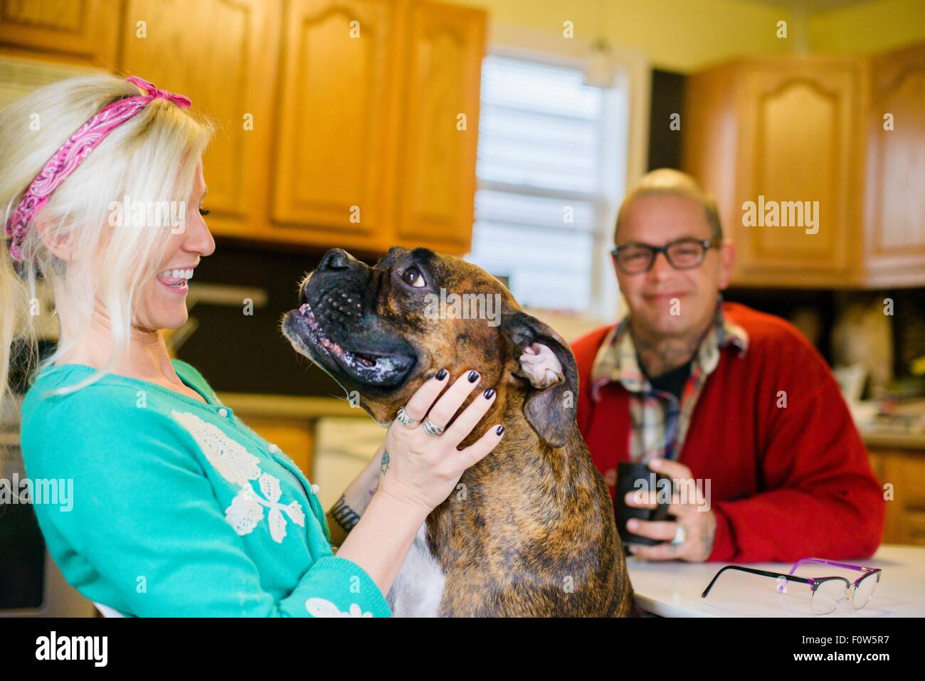 Young woman smiling at boxer dog, face to face - Stock Image