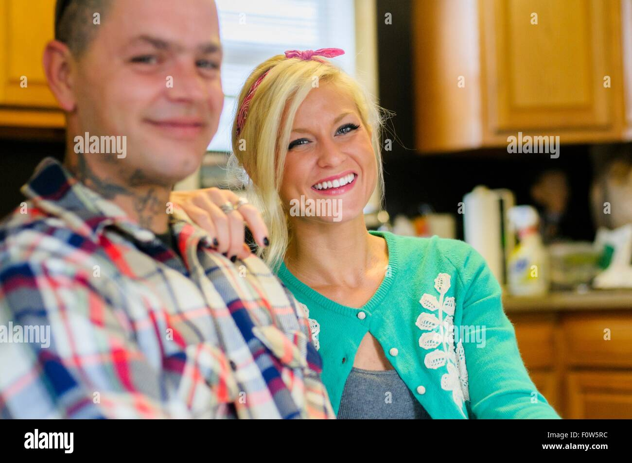 Young woman with hand on man's shoulder, smiling - Stock Image