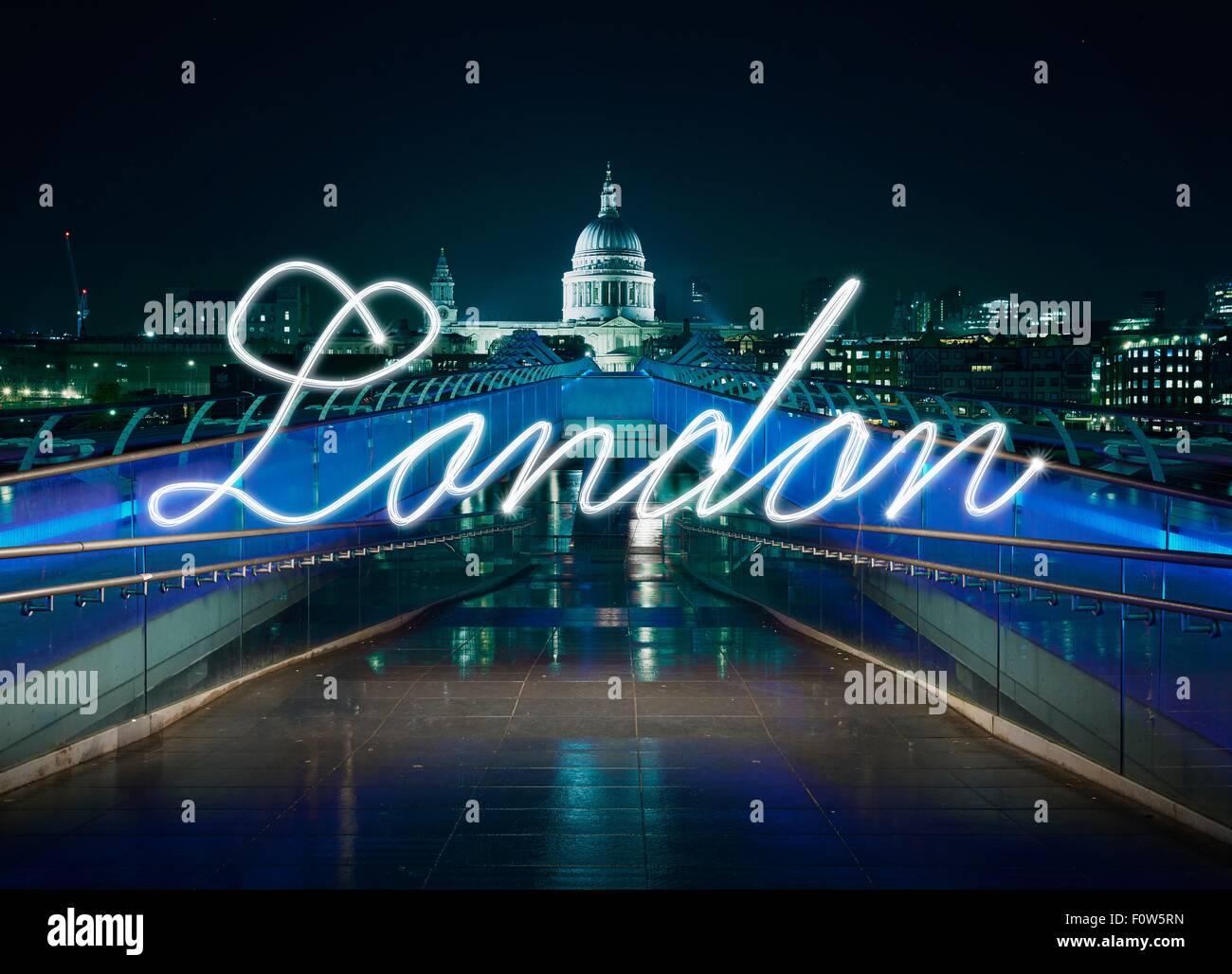 Glowing handwritten London in front of Millennium bridge at night, London, UK - Stock Image