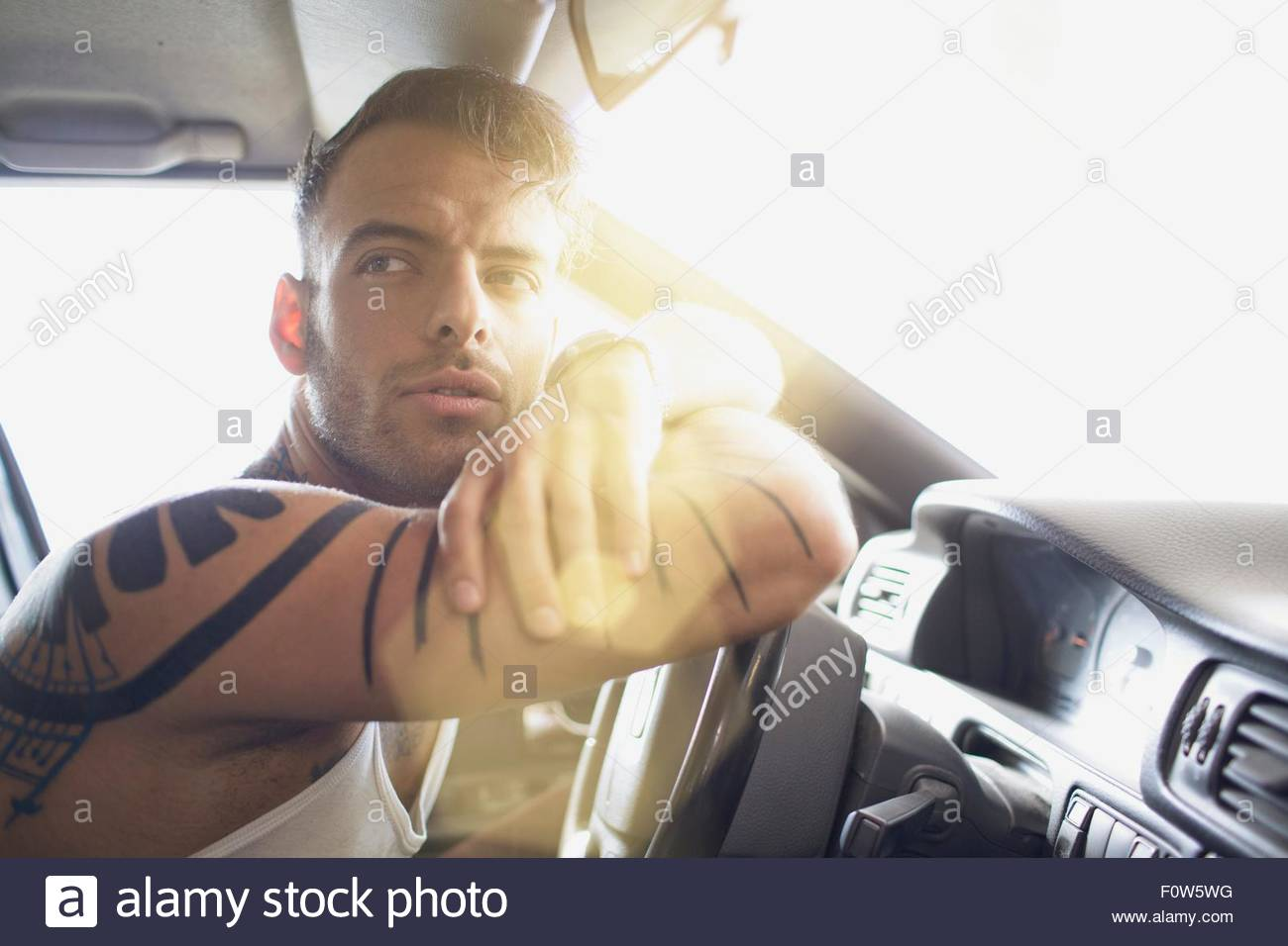 Young man arms crossed leaning against steering wheel - Stock Image
