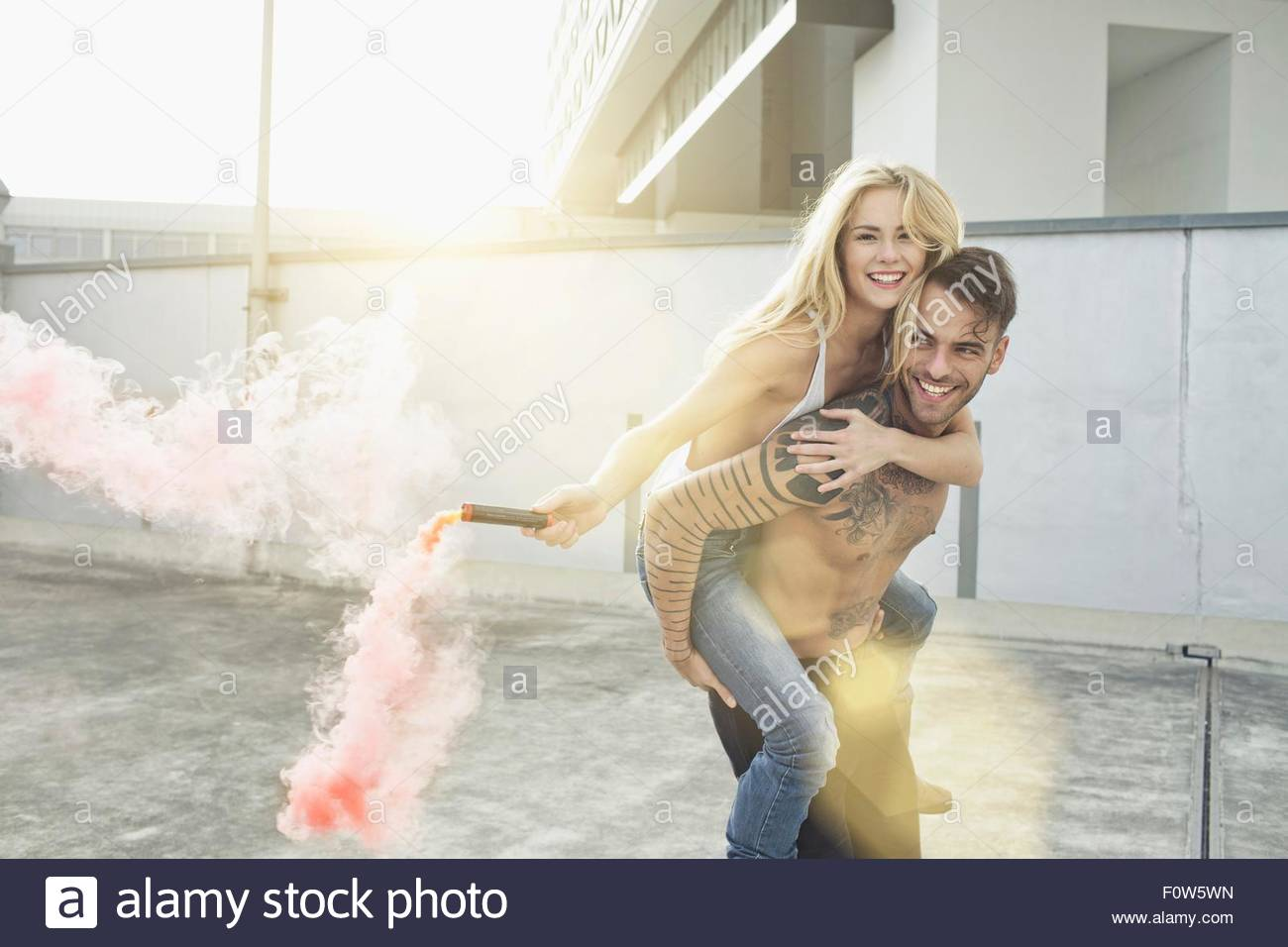 Young woman holding flare on mans back - Stock Image
