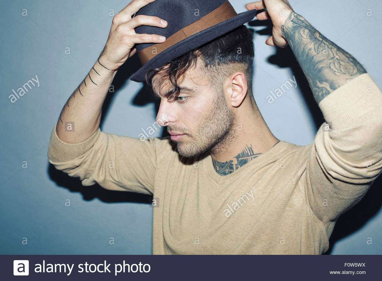 Young tattooed man putting on hat, looking away - Stock Image