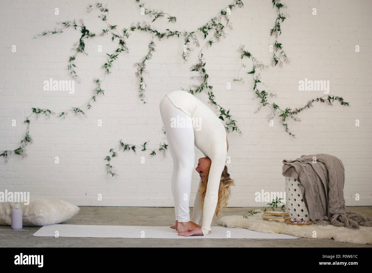 A blonde woman, in a white leotard and leggings, standing on a white mat in a room in a yoga position, bending forwards - Stock Image