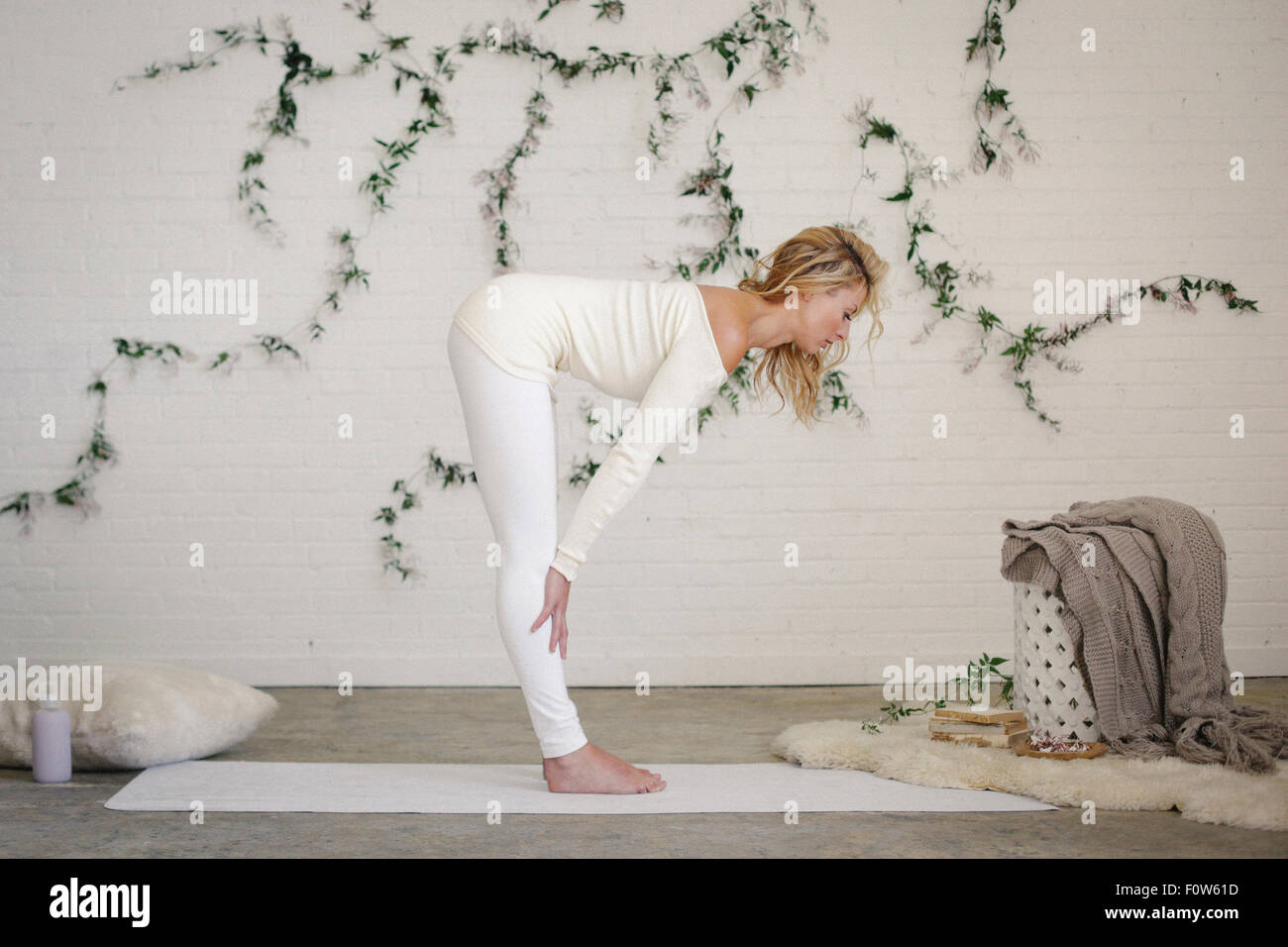 A blonde woman in a white leotard and leggings, standing on a white mat in a room,  bending forwards. - Stock Image