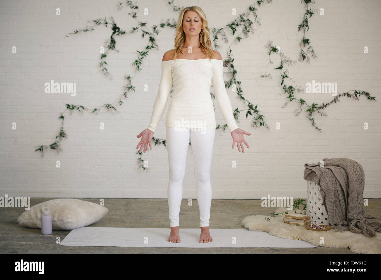 A blonde woman in a white leotard and leggings, standing on a white mat in a room. A creeper plant on the wall behind - Stock Image