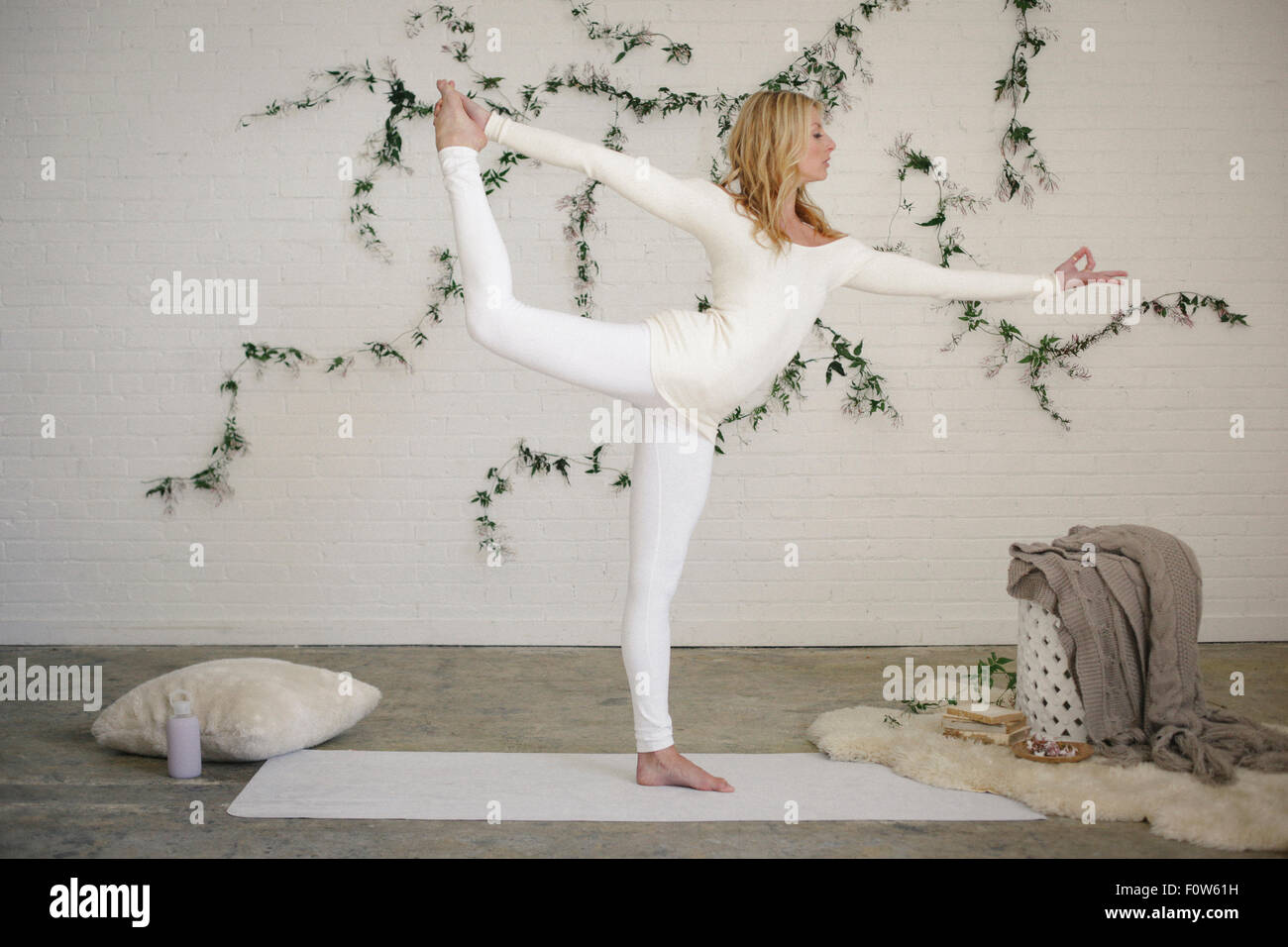 A blonde woman in a white leotard and leggings, standing on a white mat in a room, standing on one leg and arms - Stock Image