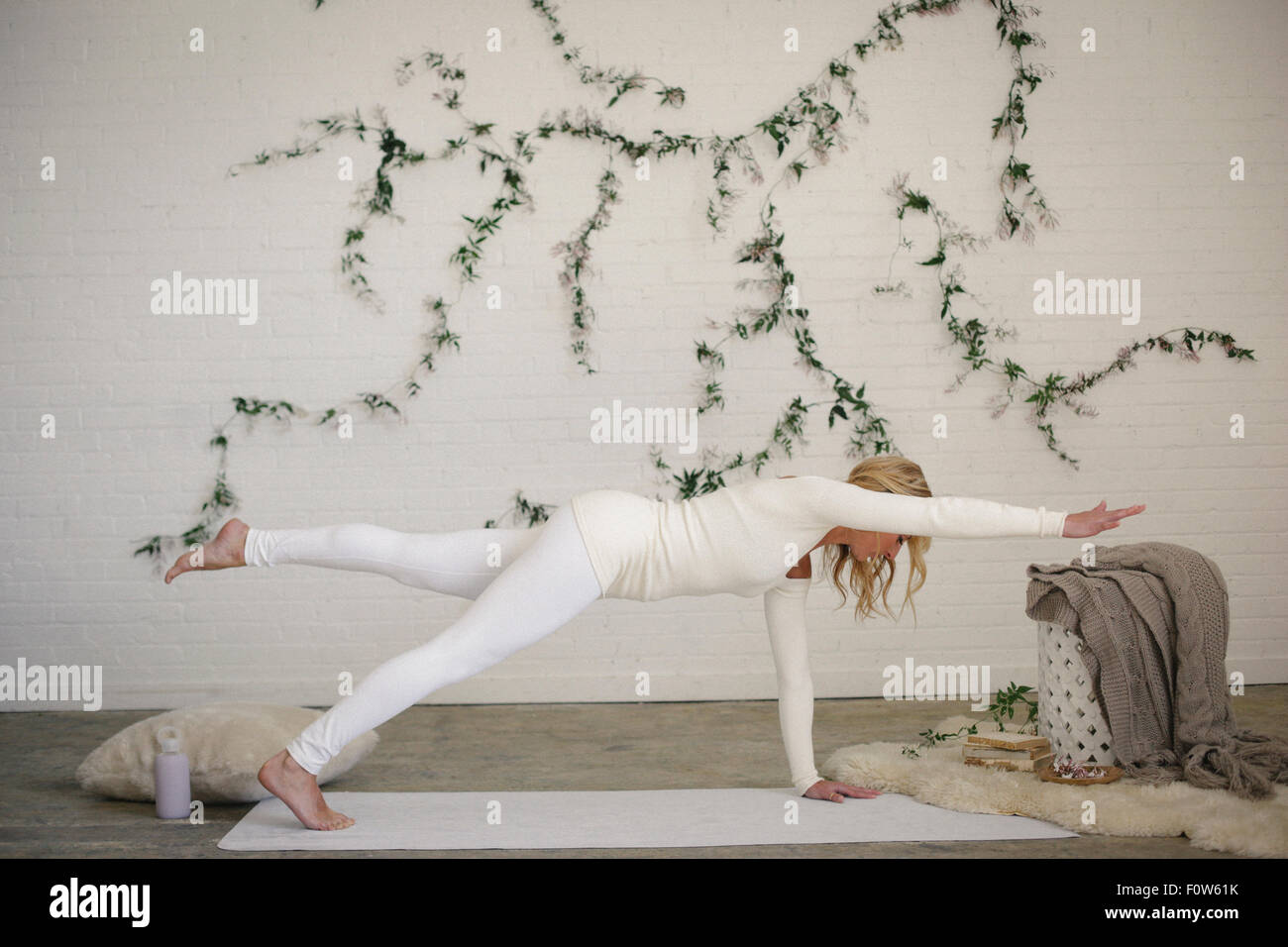 A blonde woman on a white mat in a room, her leg and arm outstretched. A creeper plant on the wall behind her. - Stock Image