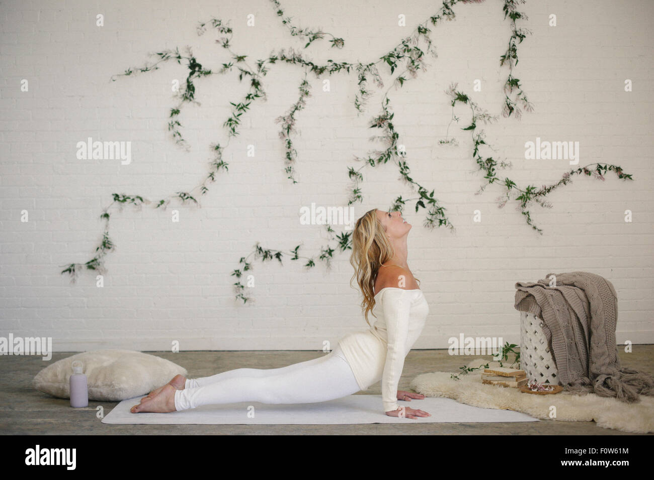 A blonde woman in a white leotard and leggings, lying on a white mat in a room, arching he back in a stretch. - Stock Image