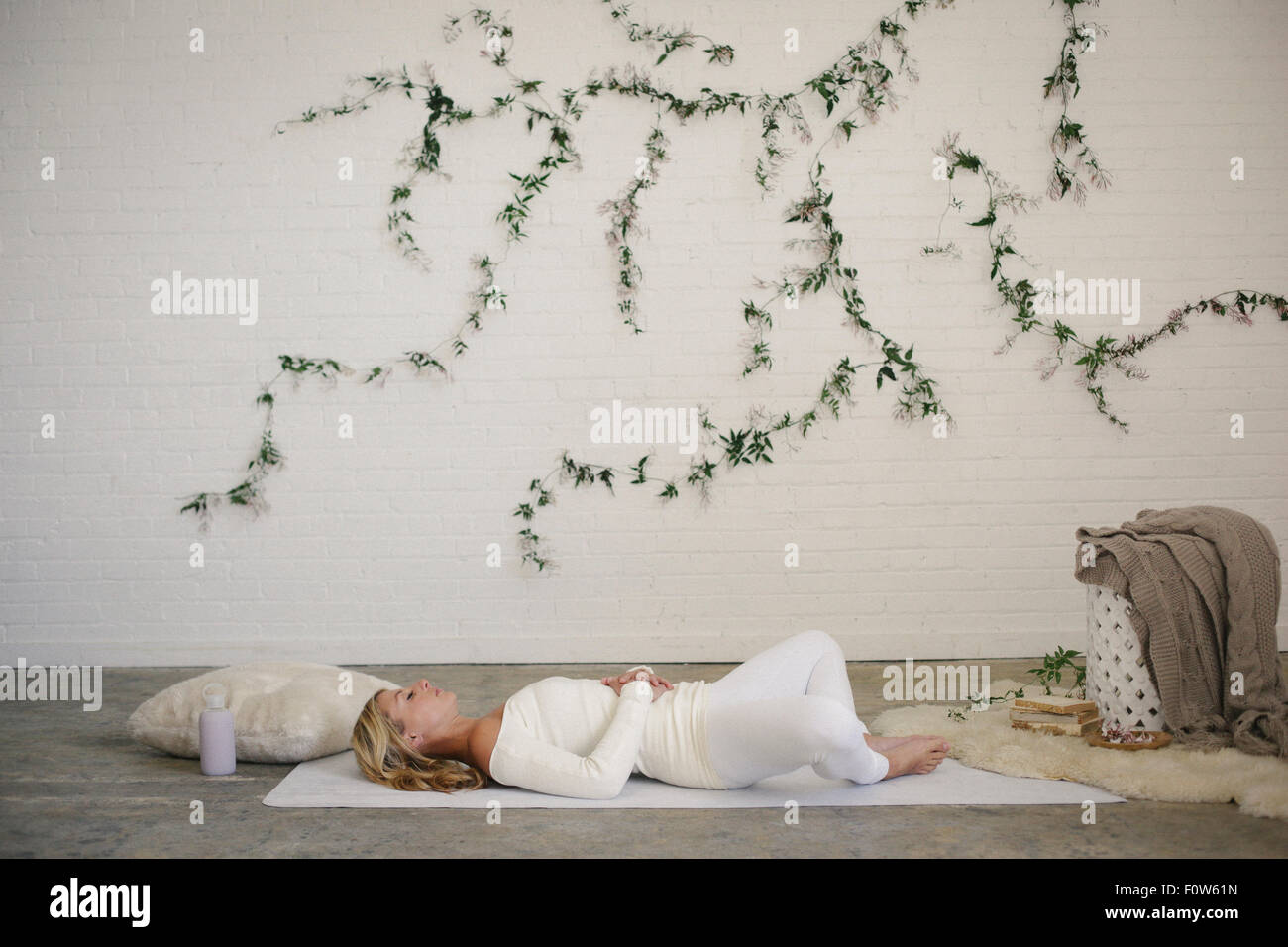 A blonde woman in a white leotard and leggings, lying on a white mat in a room. A creeper plant on the wall behind - Stock Image