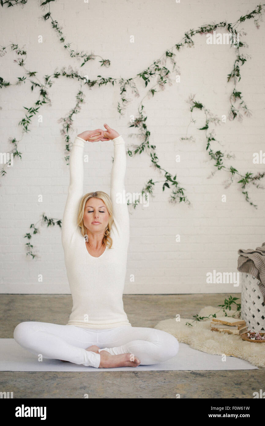 A blonde woman sitting on a white mat in a room stretching her arms. A creeper plant on the wall behind her. - Stock Image