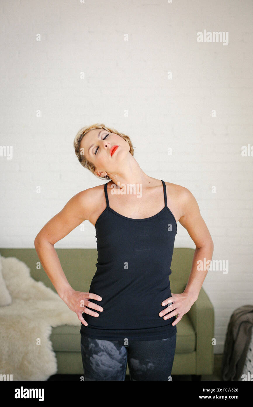 A blonde woman in a black leotard standing in a room, doing yoga, her hands on her hips, stretching her neck. - Stock Image