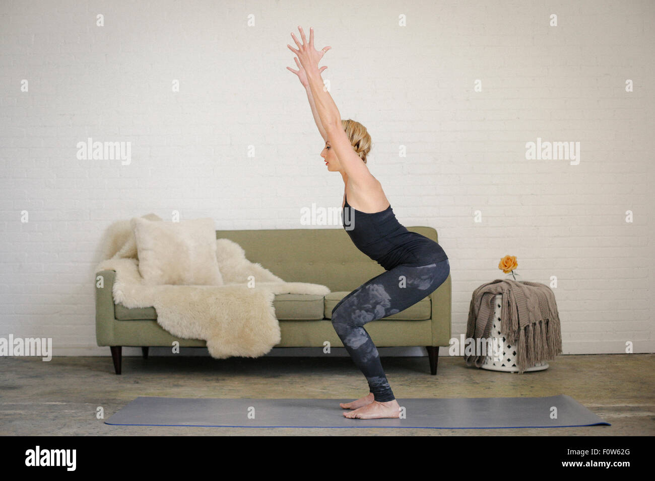 A blonde woman in leotard and leggings, standing on a yoga mat in a room, doing yoga, squatting down with her arms - Stock Image