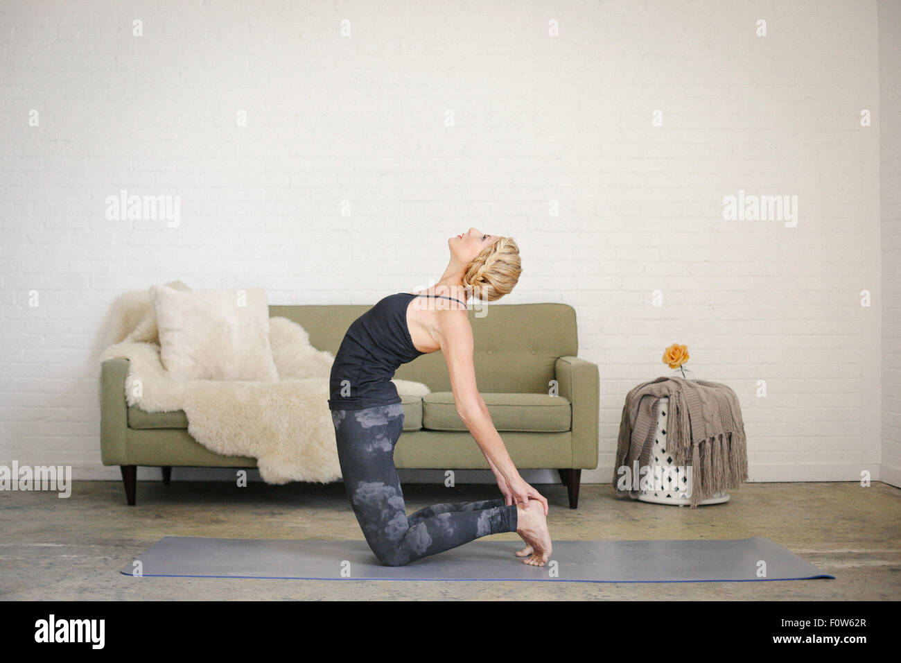 A blonde woman kneeling on a yoga mat in a room, doing yoga, bending backwards with her hands touching her heels. - Stock Image