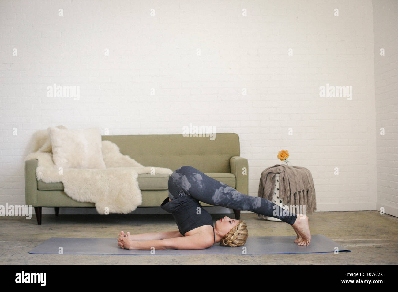 A blonde woman in a black leotard and leggings, lying on a yoga mat in a room, doing yoga, her legs bent down over - Stock Image