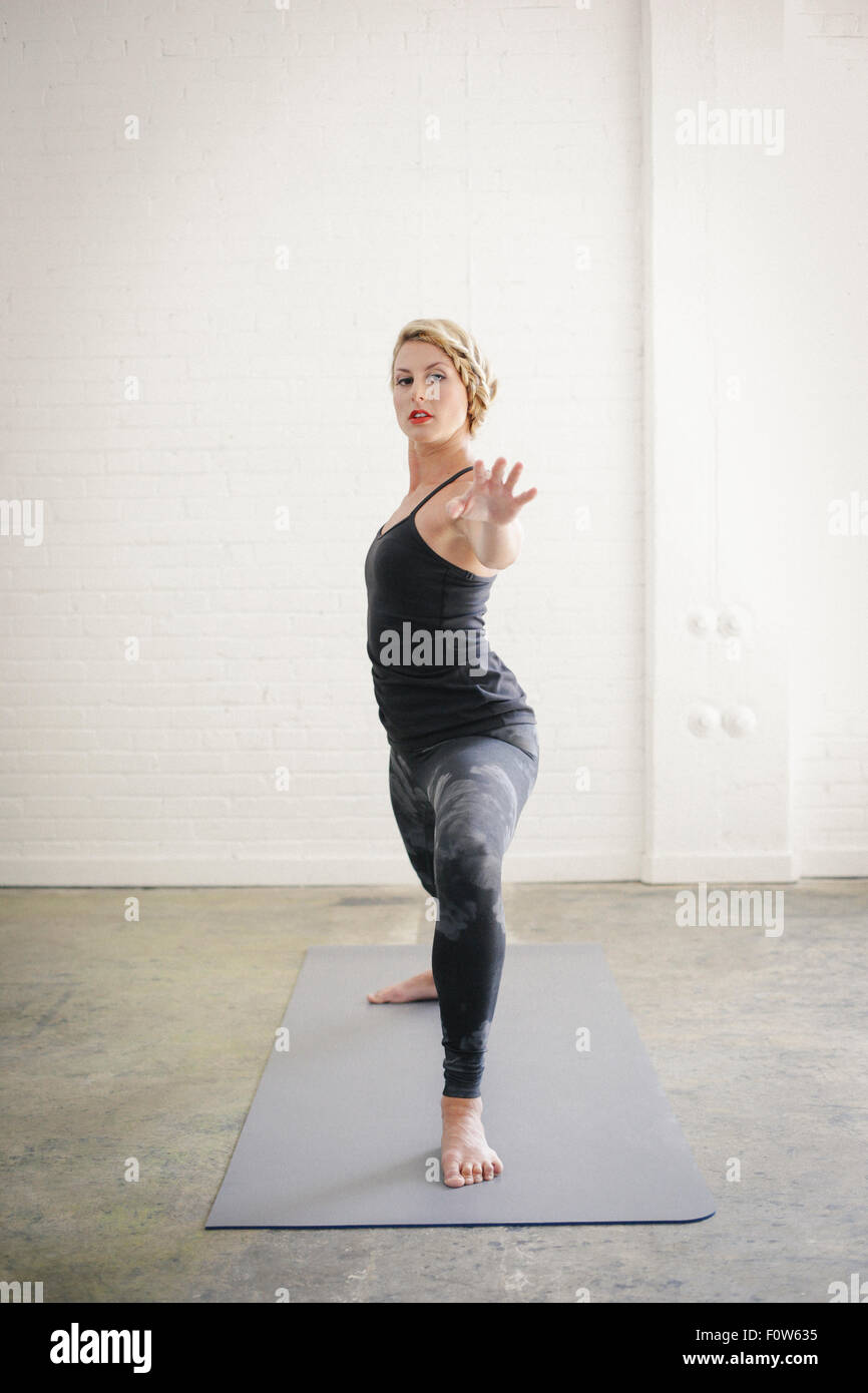 A blonde woman in a black leotard and leggings bending her knees in a lunge with her arms outstretched. - Stock Image