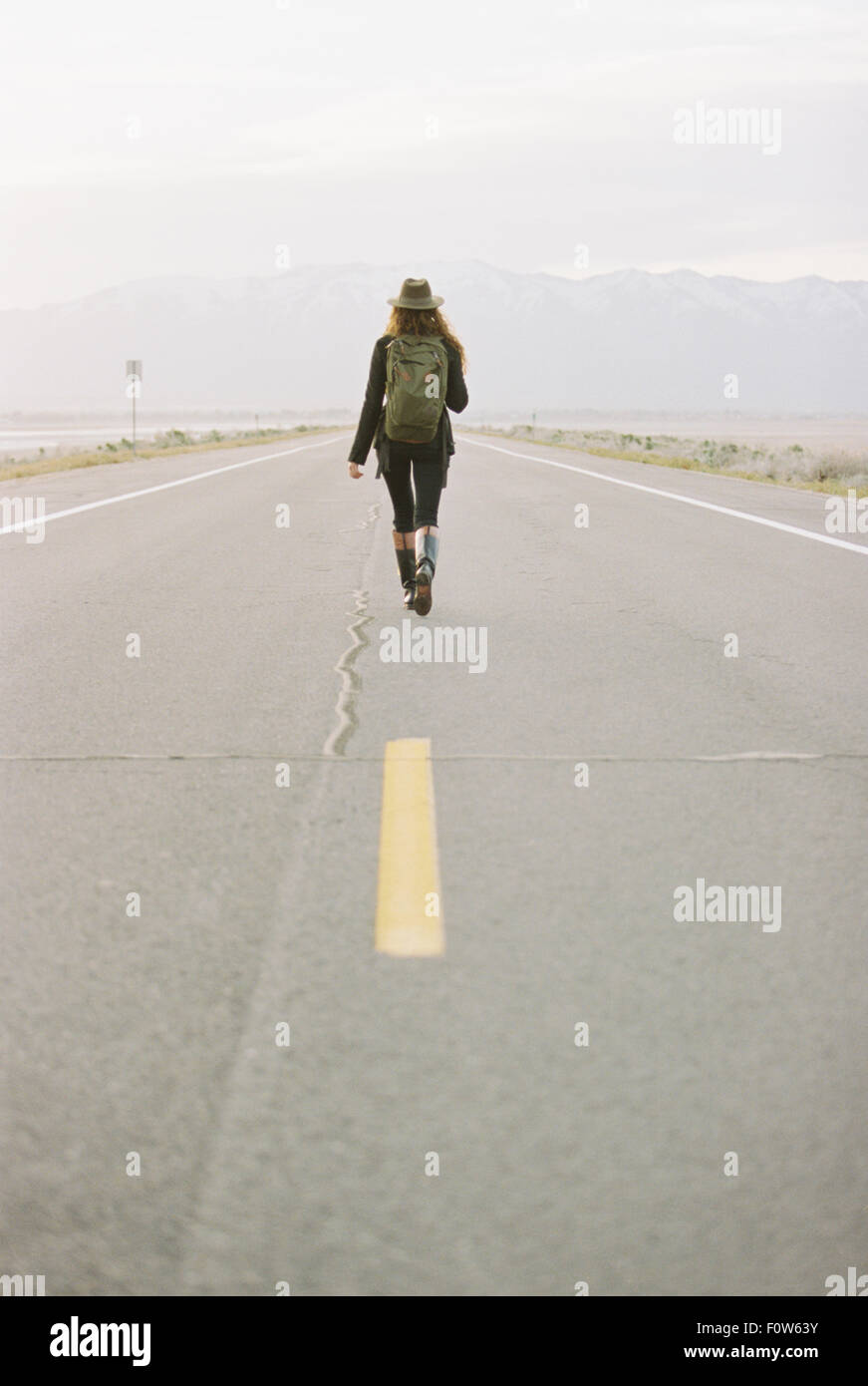 A woman carrying a backpack walking down the centre line of a  country road. - Stock Image