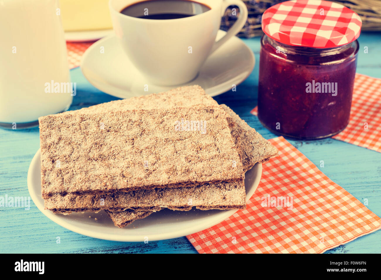 closeup of crispbread in a plate, a cup of coffee, a bottle with milk and a jar of jam on a rustic blue wooden table, - Stock Image
