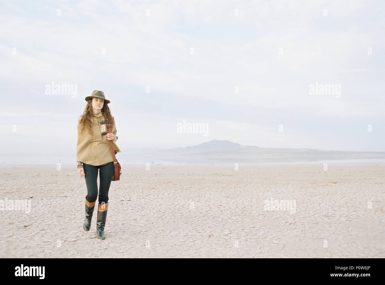 A woman with brown, long and curly hair walking through a desert plain, wearing a hat and carrying a leather bag. - Stock Image
