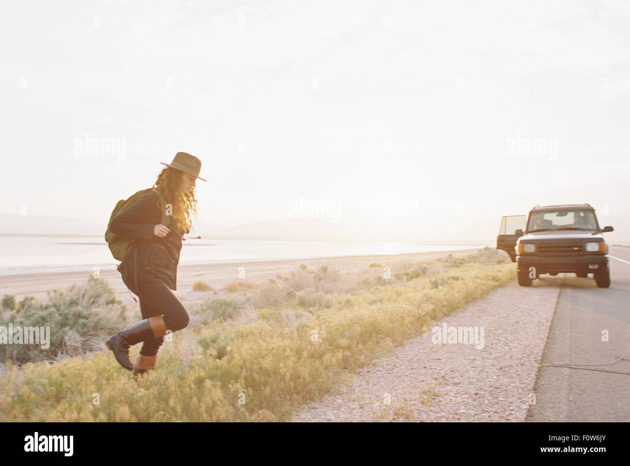 A woman wearing a hat and carrying a backpack near a 4x4 car, - Stock Image